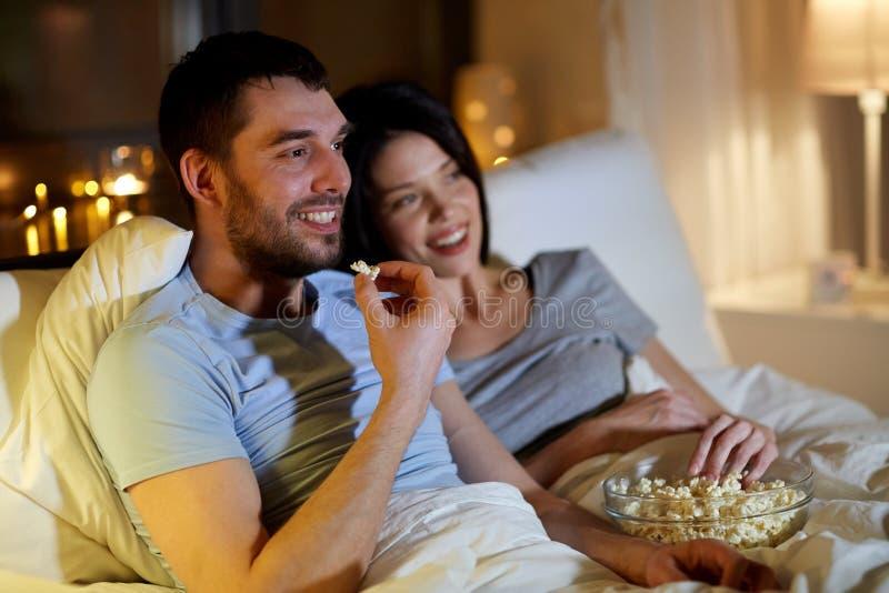 Paar die met popcorn op TV thuis letten bij nacht stock foto