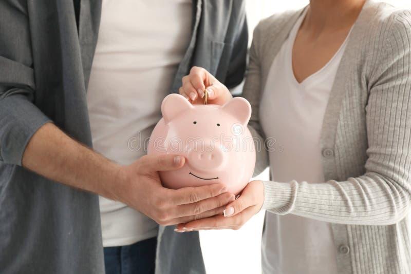Paar die muntstuk zetten in spaarvarken, close-up De besparingenconcept van het geld royalty-vrije stock afbeeldingen