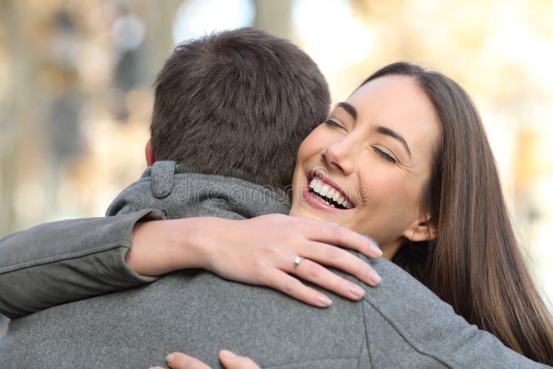 Paar die na gelukkig voorstel in de straat koesteren stock afbeeldingen