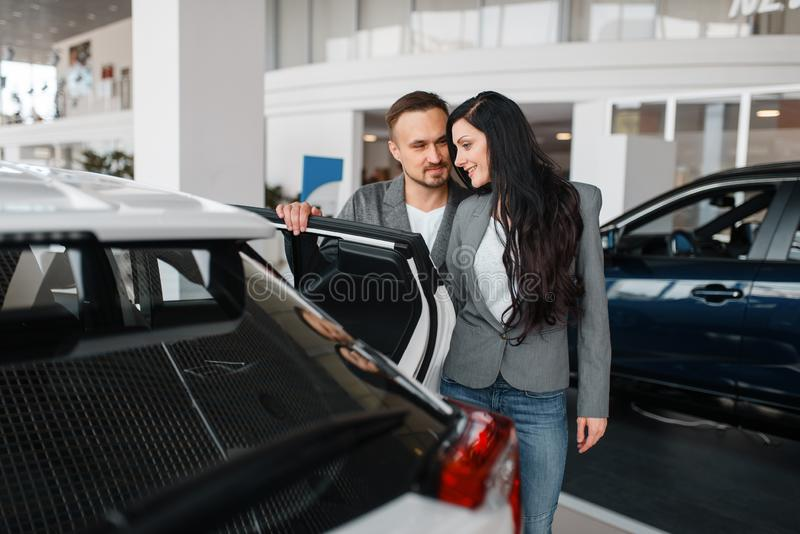 Paar die nieuwe auto in toonzaal kopen stock foto's