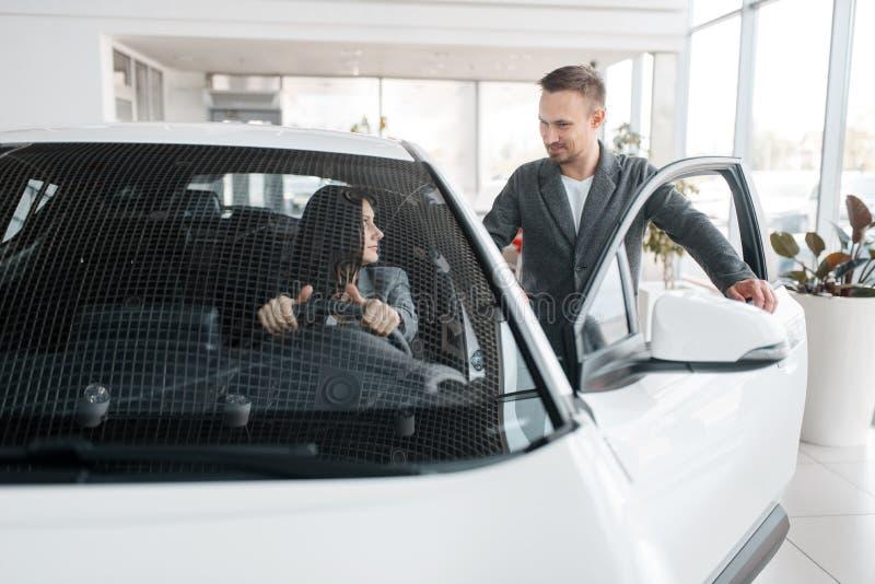 Paar die nieuwe auto, vrouw achter het wiel kopen stock afbeelding