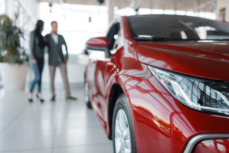 Paar die nieuwe rode auto in toonzaal kopen royalty-vrije stock foto