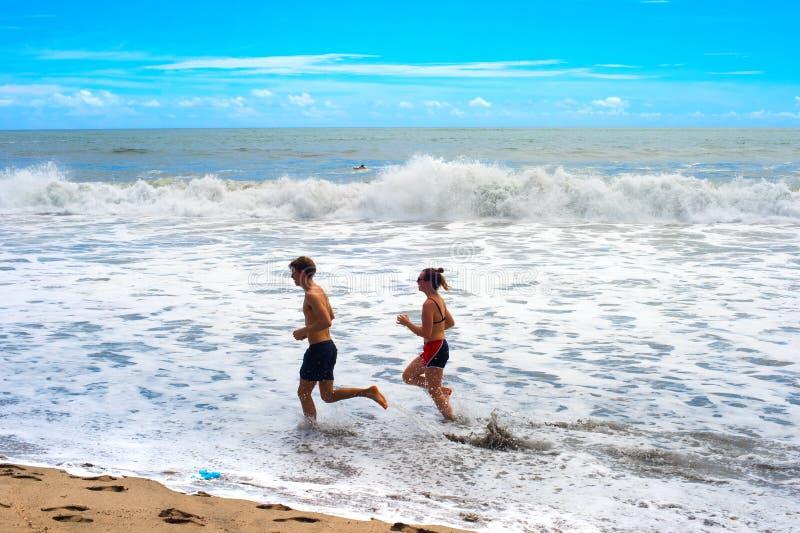 Paar die oceaanstrand Bali in werking stellen royalty-vrije stock afbeelding