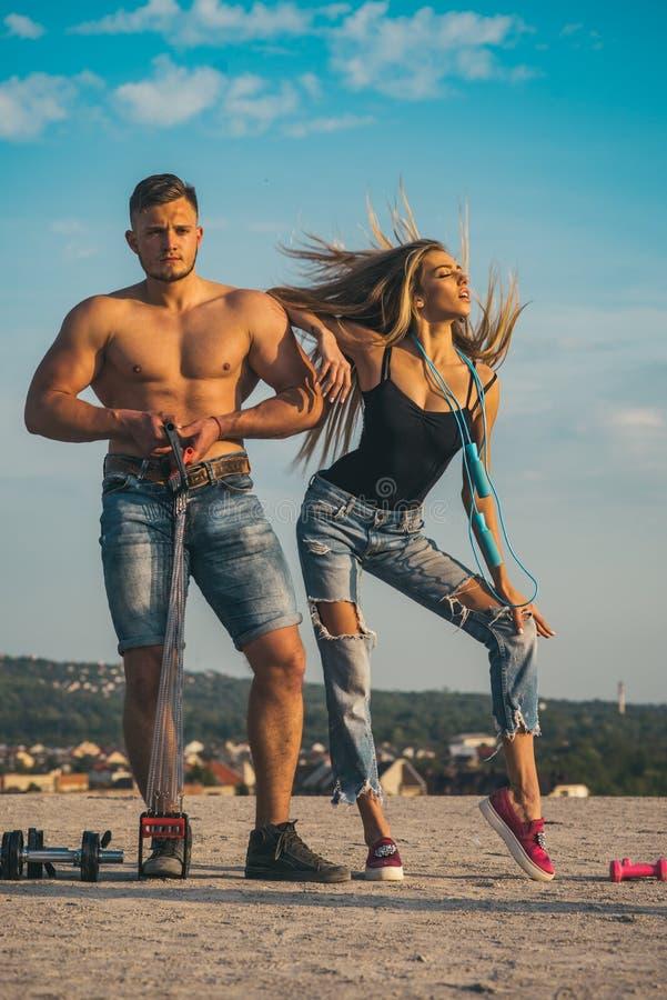 Paar die omhoog spieren in openlucht pompen Training achter elkaar, sport en fitness concept Sexy blond meisje en spierkerel ople stock afbeelding