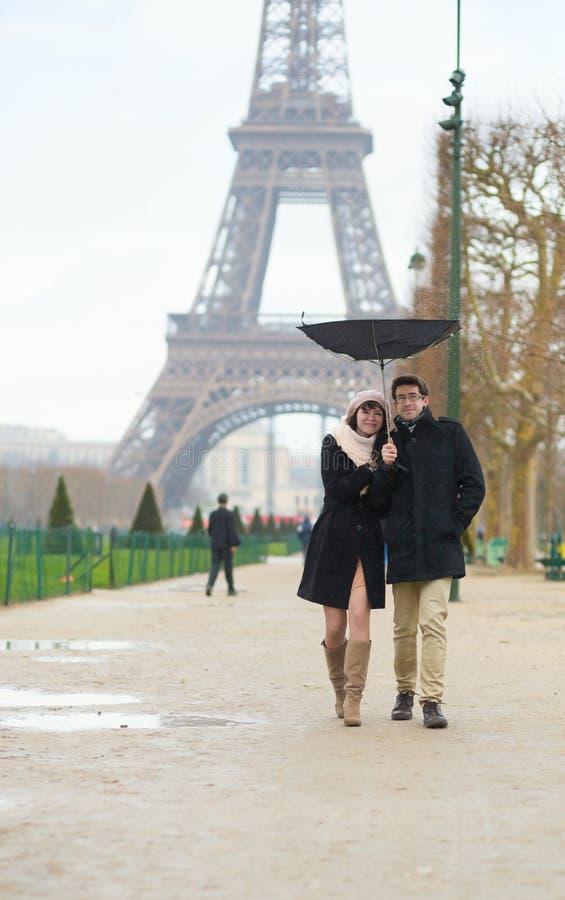 Paar die onder de regen met gebroken paraplu lopen royalty-vrije stock foto