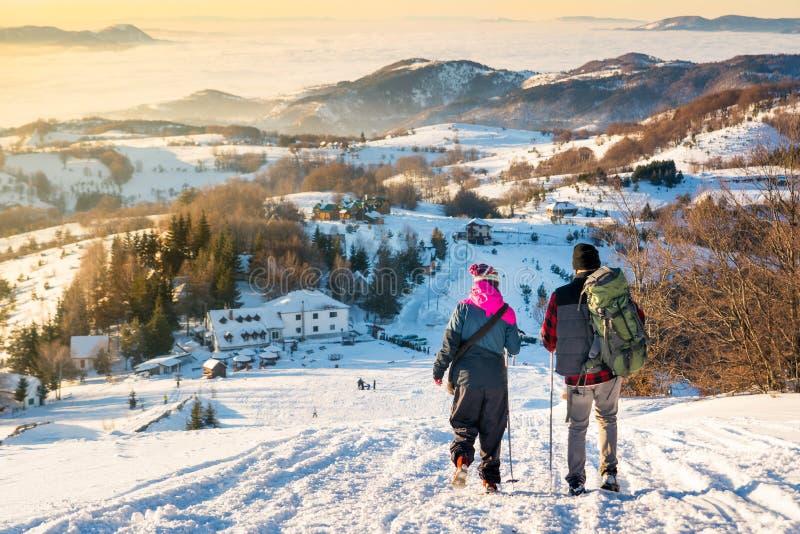 Paar die onderaan de sneeuwberg in zonsondergangtijd lopen royalty-vrije stock foto's