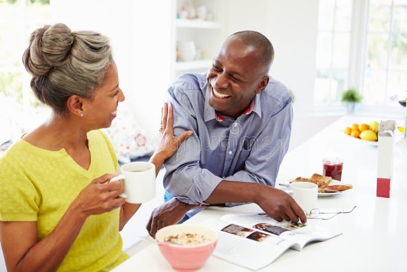 Paar die Ontbijt hebben en Tijdschrift in Keuken lezen stock afbeeldingen