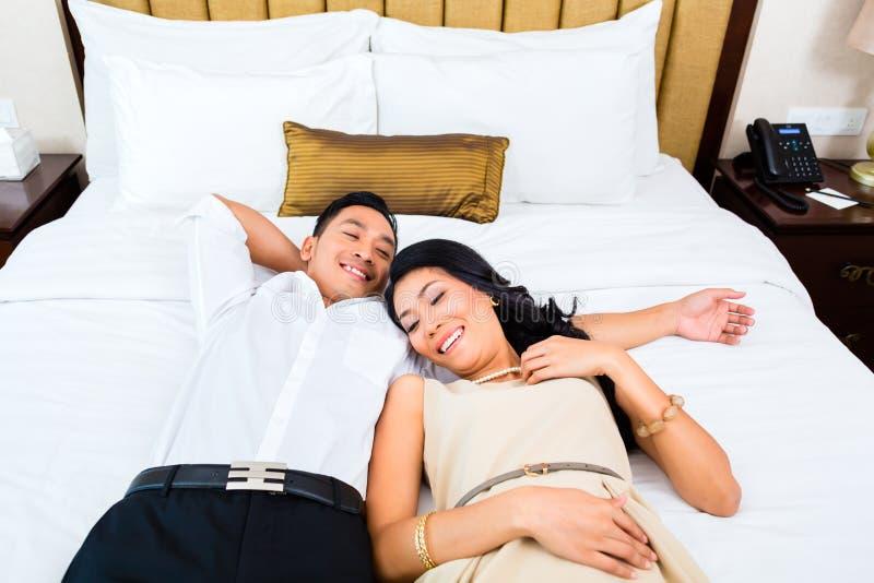 Paar die op bed in hotelruimte liggen royalty-vrije stock afbeelding