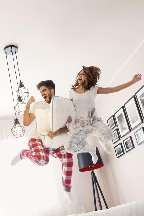 Paar die op bed springen royalty-vrije stock fotografie