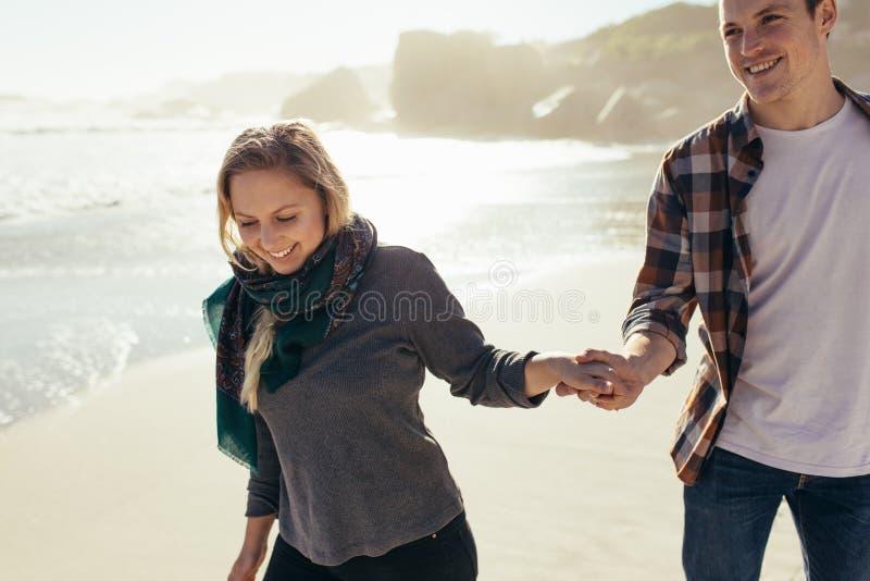 Paar die op de handen van de strandholding lopen stock foto's