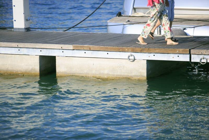 Paar die op de havenpijler lopen stock foto