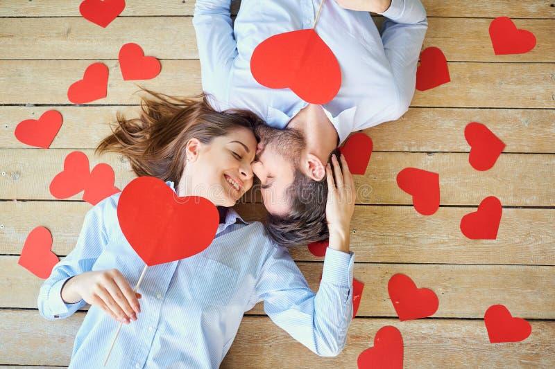 Paar die op de houten vloer met harten hierboven mening liggen van stock fotografie