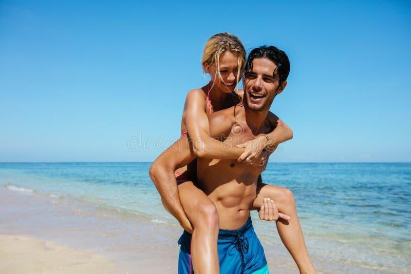 Paar die op de rug van rit op het strand genieten stock fotografie