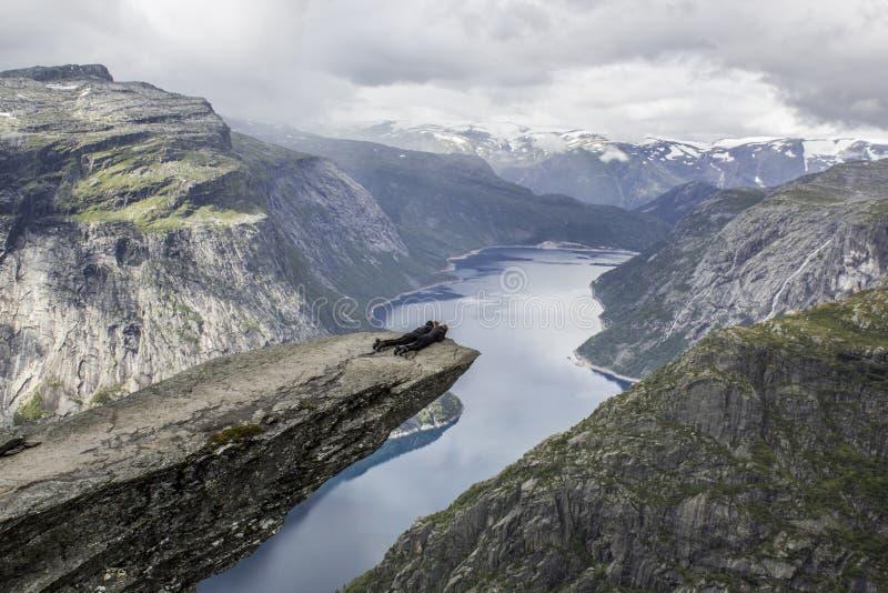 Paar die op de tongrots van de trolltungasleeplijn ` s liggen, Noorwegen stock fotografie