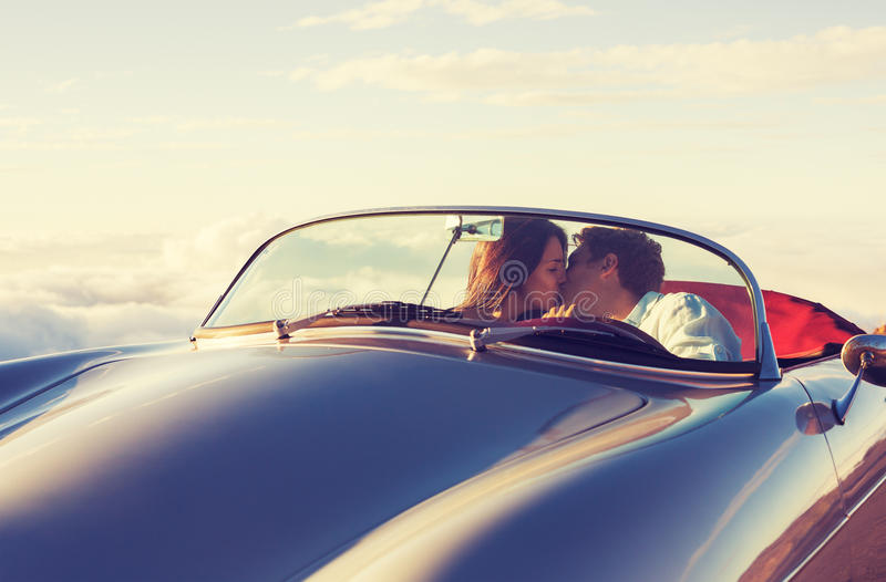 Paar die op de Zonsondergang in Klassieke Uitstekende Auto letten stock foto's