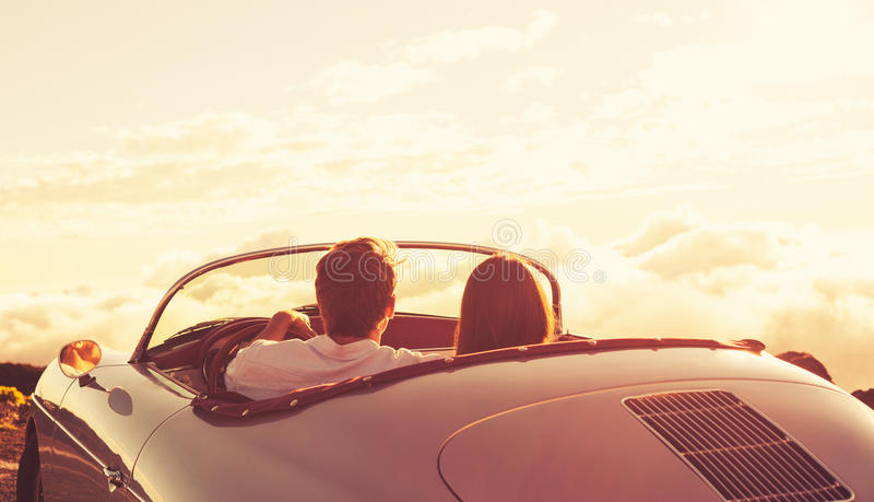 Paar die op de Zonsondergang in Klassieke Uitstekende Auto letten stock foto