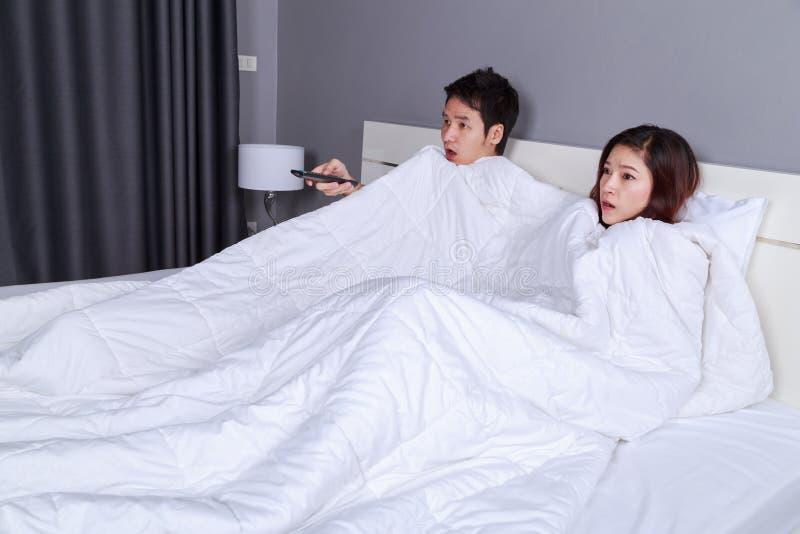 Paar die op doen schrikken film met TV-afstandsbediening letten onder bl stock foto's