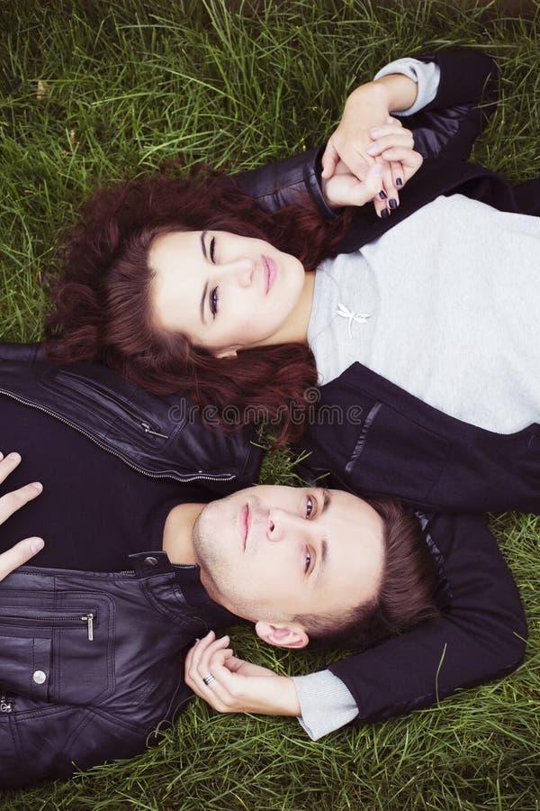 Paar die op een groen gras leggen en handen houden stock foto's