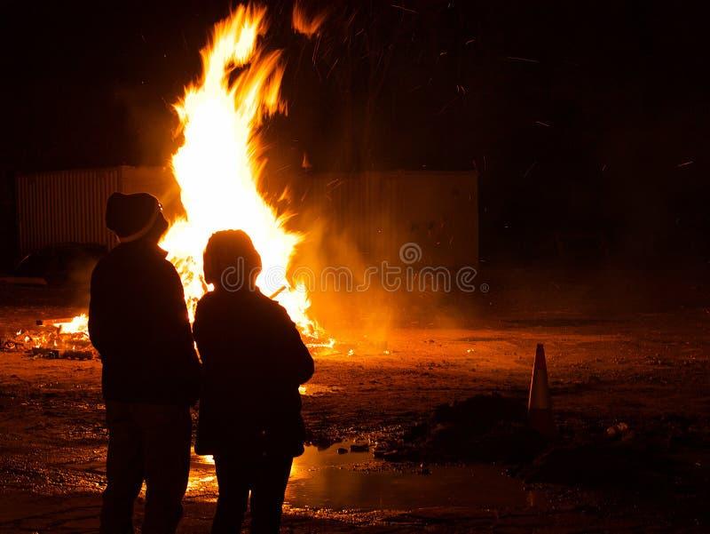 Paar die op een groot vuur letten bij nacht stock afbeelding