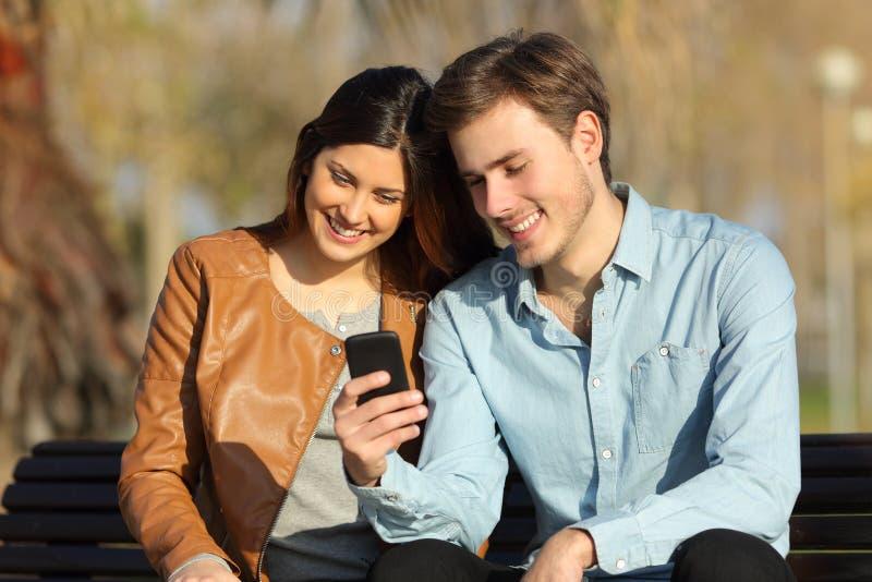 Paar die op een slimme telefoonzitting op een bank letten stock foto