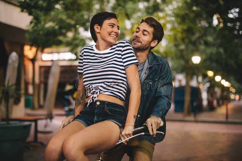 Paar die op fiets in de stad genieten van stock foto