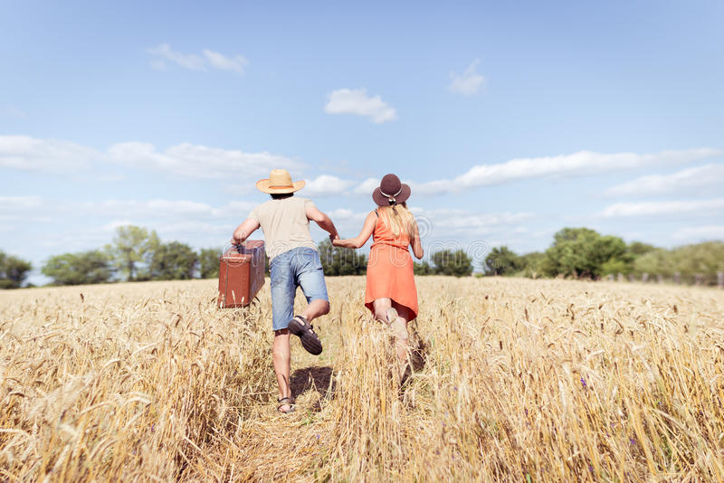 Paar die op gebied, mensenholding in zijn hand uitstekende koffer lopen op blauwe de hemel in openlucht achtergrond van het platt stock foto