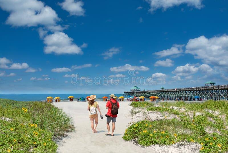 Paar die op het mooie strand op de zomervakantie lopen stock afbeelding
