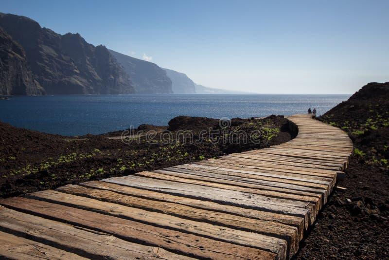 Paar die op houten weg aan oceaan lopen royalty-vrije stock foto