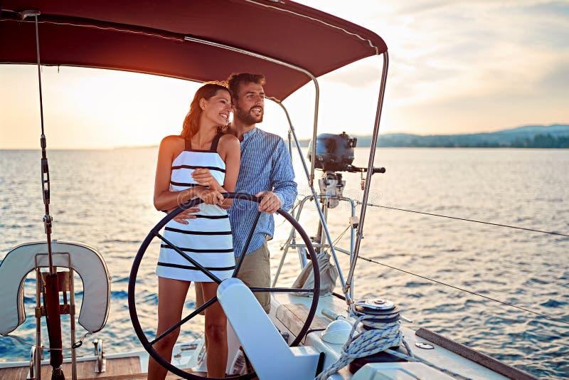 Paar die op luxeboot bij zonsondergang op vakantie genieten van stock afbeelding