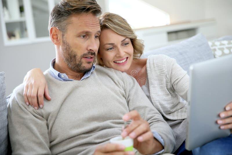 Paar die op middelbare leeftijd gebruikend tablet genieten van royalty-vrije stock afbeelding