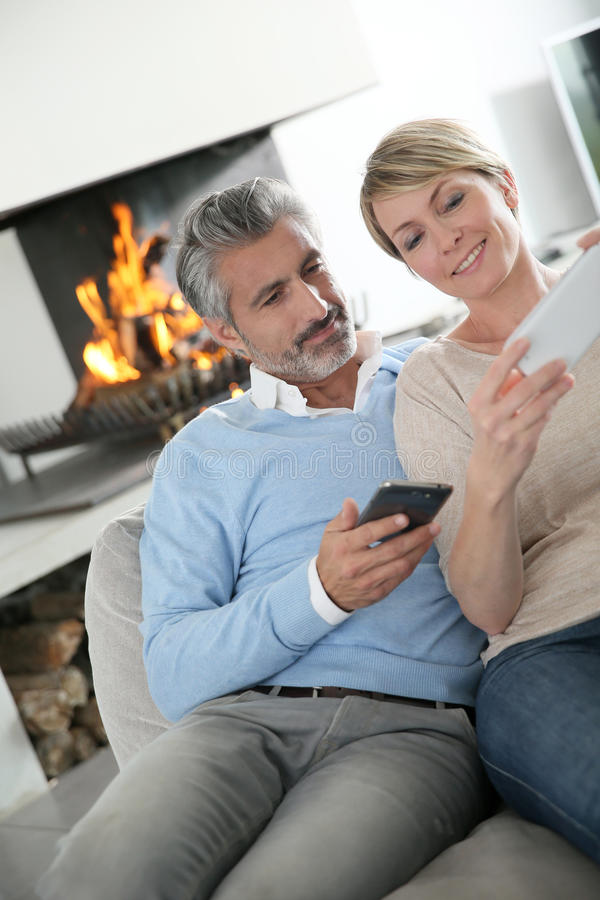 Paar die op middelbare leeftijd hun smartphones thuis gebruiken stock foto