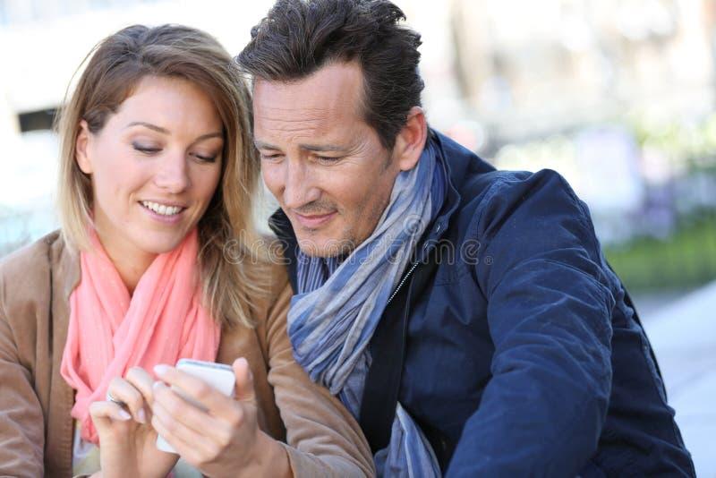 Paar die op middelbare leeftijd in openlucht smartphone gebruiken stock foto's