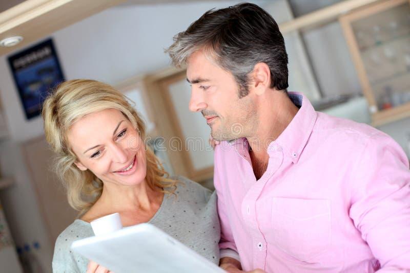 Paar die op middelbare leeftijd tablet in de keuken gebruiken stock afbeeldingen
