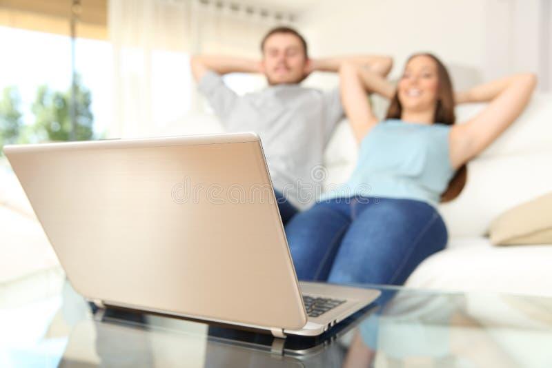 Paar die op online laptop thuis ontspannen inhoud letten royalty-vrije stock afbeeldingen
