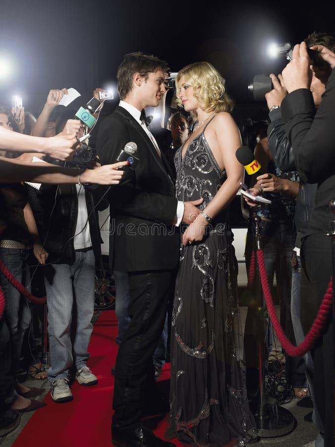 Paar die op Rood die Tapijt omhelzen door Paparazzi wordt omringd royalty-vrije stock afbeelding