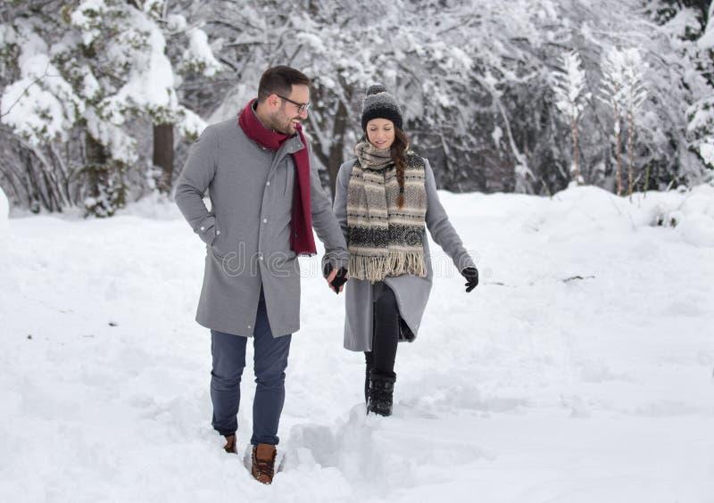 Paar die op sneeuw in bos lopen royalty-vrije stock afbeeldingen