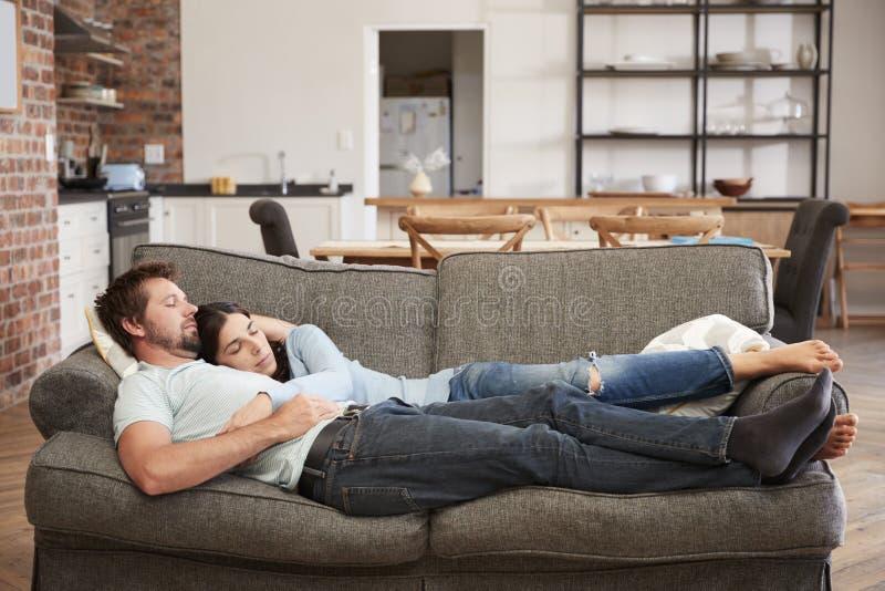 Paar die op Sofa In Open Plan Lounge rusten stock fotografie