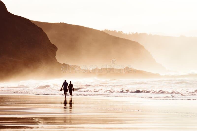 Paar die op strand met mist lopen royalty-vrije stock foto