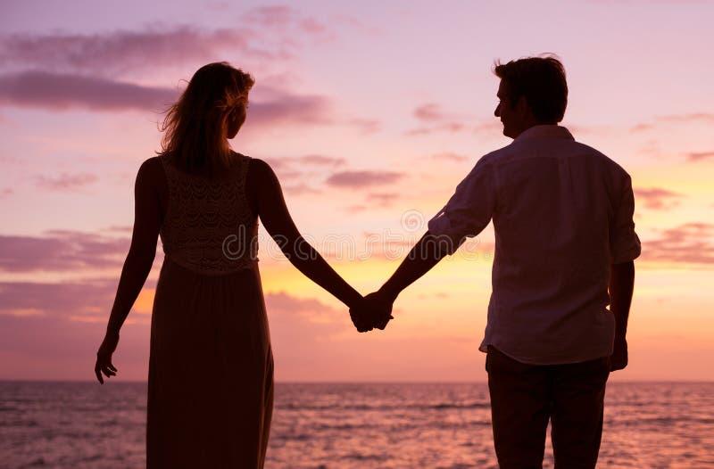 Paar die op tropische zonsondergang letten royalty-vrije stock foto's