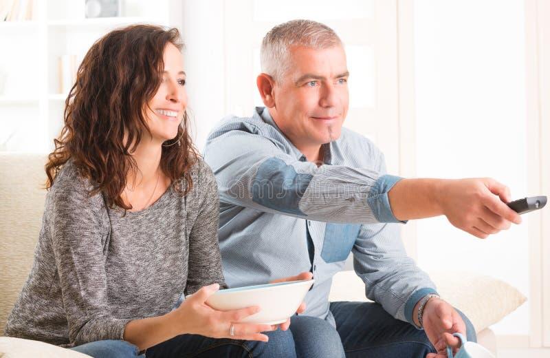 Paar die op TV in hun woonkamer letten royalty-vrije stock foto's