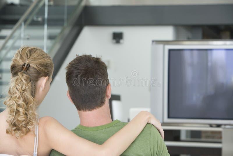 Paar die op TV thuis letten royalty-vrije stock afbeelding