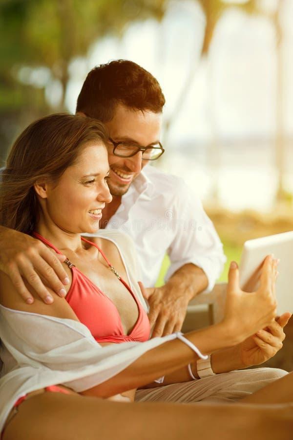 Paar die op vakantie met familie over tabletpc communiceren stock foto's