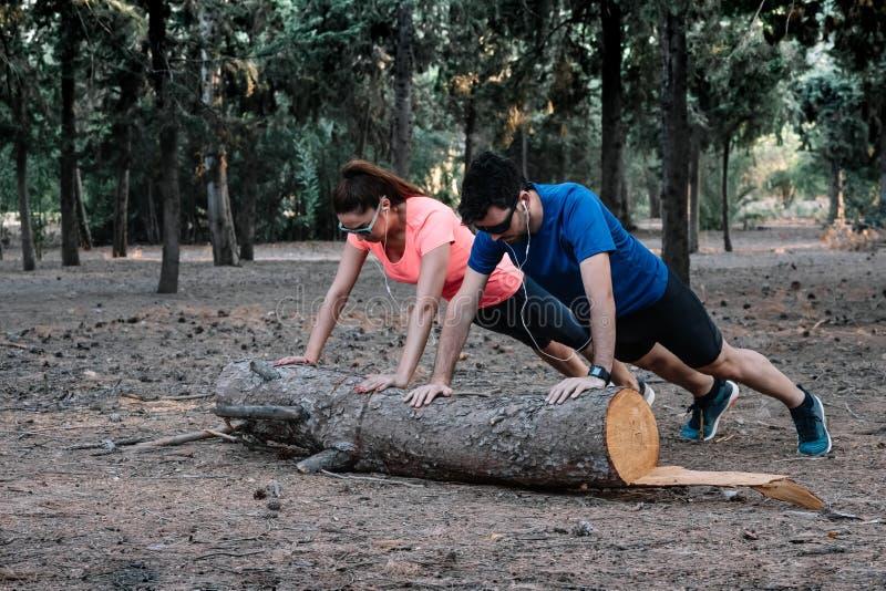 Paar die opdrukoefeningen op login doen een park royalty-vrije stock foto