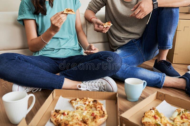 Paar die pizzazitting op vloer eten royalty-vrije stock foto's