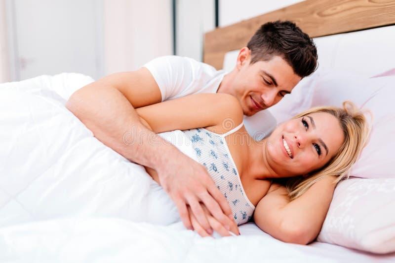 Paar die pret in bed en het glimlachen hebben royalty-vrije stock fotografie