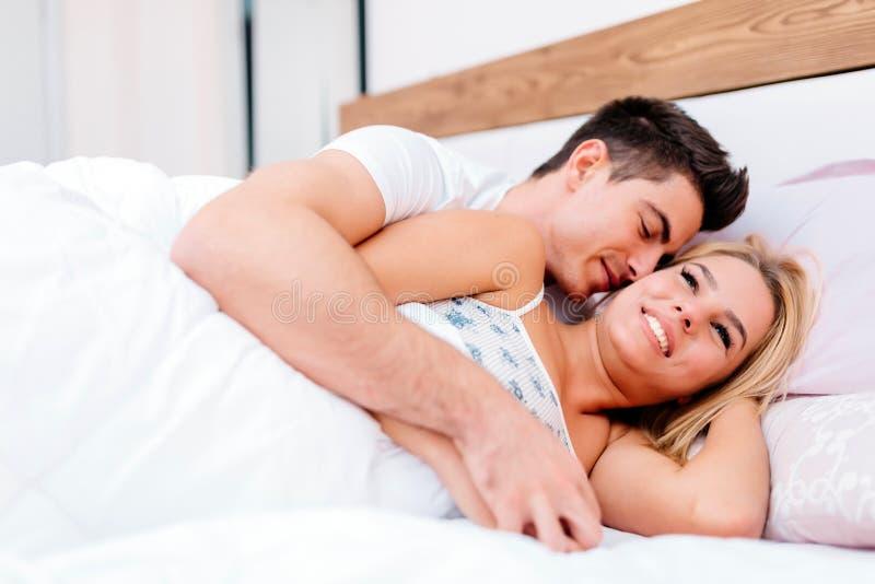 Paar die pret in bed en het glimlachen hebben stock foto