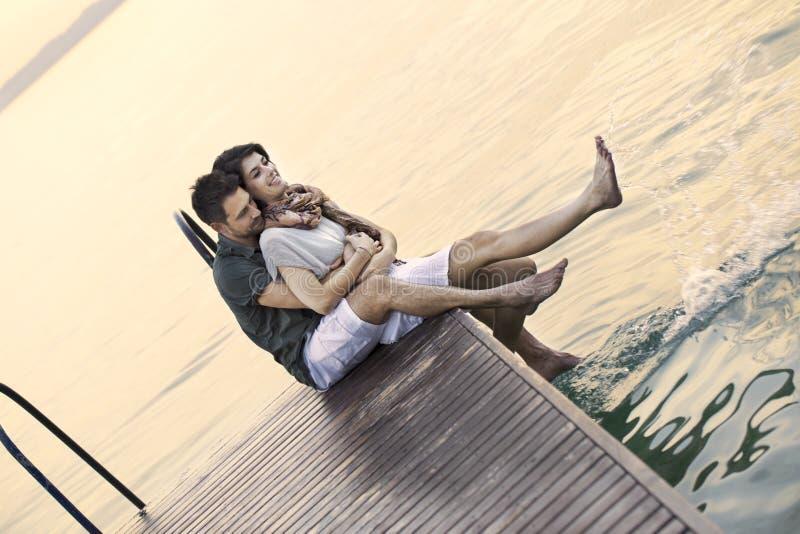 Paar die pret gezet op een boardwak met een mooie meermening hebben stock foto's