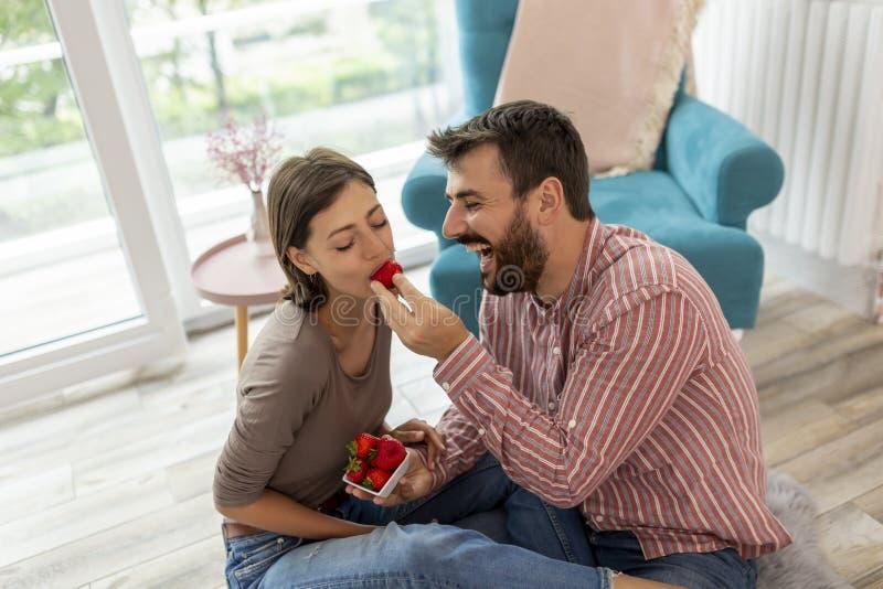 Paar die pret hebben die aardbeien eten royalty-vrije stock afbeeldingen