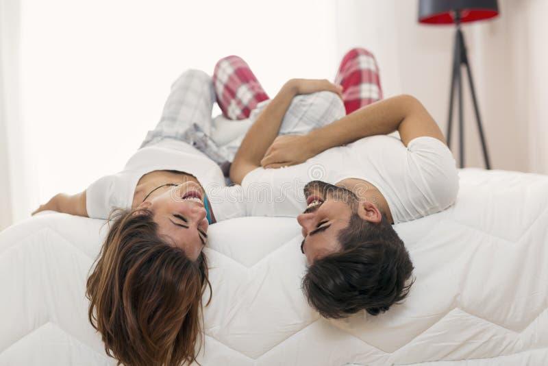 Paar die pret hebben die in bed liggen stock foto's