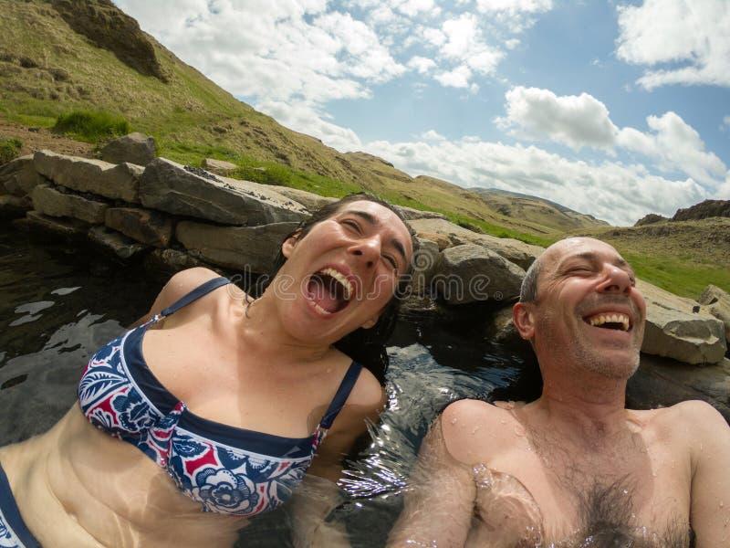 Paar die pret hebben en in een hete pool in Hrunalaug, IJsland ontspannen stock foto